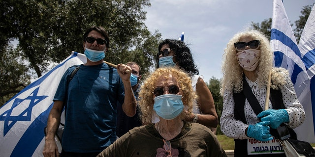 Supporters of Prime Minister Benjamin Netanyahu wear a masks amid concerns over the country's coronavirus outbreak during a protest by in front of Israel's Supreme Court in Jerusalem, Sunday, May 3, 2020. (AP Photo/Tsafrir Abayov)
