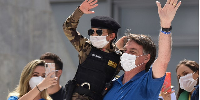 Brazil's President Jair Bolsonaro, wearing a mask against the spread of the new coronavirus, carries a child dressed in military policeman's uniform during a protest against the Supreme Court and Brazil's National Congress, to back his open-the-economy drive amid the pandemic, in Brasilia, Brazil, Sunday, May 17, 2020.