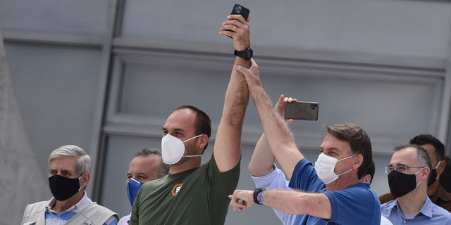 Brazil's President Jair Bolsonaro, right, wearing a mask against the spread of the new coronavirus, raises the arm of his son Eduardo Bolsonaro during a protest against the Supreme Court and Brazil's National Congress, and to back his open-the-economy drive amid the pandemic, in Brasilia, Brazil, Sunday, May 17, 2020. Bolsonaro greeted hundreds of supporters who gathered at the presidential residence to back his open-the-economy drive even as the COVID-19 pandemic sweeps across the country. (AP Photo/Andre Borges)