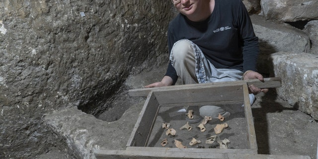 Tehila Sadiel holding the finds. (Shai Halevi-Israel Antiquities Authority)