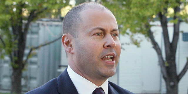 Australian Treasurer Josh Frydenberg addresses the media as he arrives at Parliament House in Canberra Australia