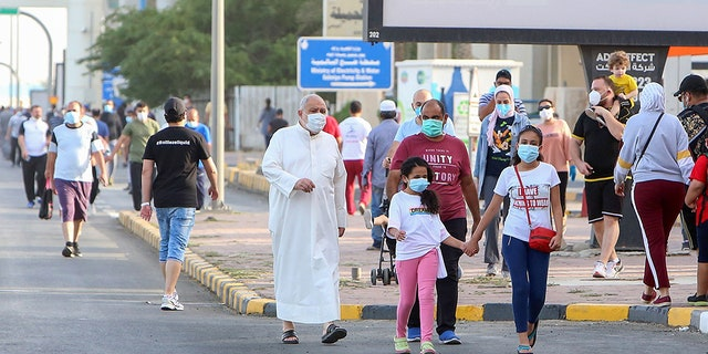 Mask-clad residents walk in a neighborhood of Kuwait City on May 12, as authorities allowed people to exercise for two hours under a nationwide lockdown due to the COVID-19 pandemic. (Photo by YASSER AL-ZAYYAT / AFP)