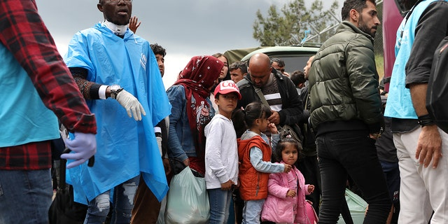 Migrants from the Moria camp wait to board busses to the port, from where they will be transferred to the mainland as a precaution against the spread of the coronavirus disease (COVID-19) outbreak, on the island of Lesbos, Greece, May 3, 2020. REUTERS/Elias Marcou - RC21HG917AWW