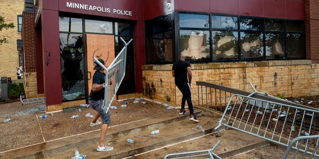 Protesters damage properties at the Minneapolis 3rd Police Precinct in Minneapolis on May 27. The mayor of Minneapolis called Wednesday for criminal charges against the white police officer seen on video kneeling against the neck of a handcuffed black man who complained that he could not breathe and died in police custody. (Carlos Gonzalez/Star Tribune via AP)