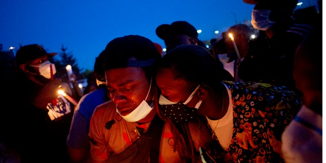 Maalik Mitchell, center left, shedding tears as he said goodbye to his father, Calvin Munerlyn, during a vigil Sunday in Flint, Mich. (Jake May/The Flint Journal via AP)