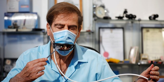 Meir Gitelis, co-developer of an Israeli company, eats while wearing a mask fitted with a mechanical mouth that opens to enable diners to eat without taking it off.