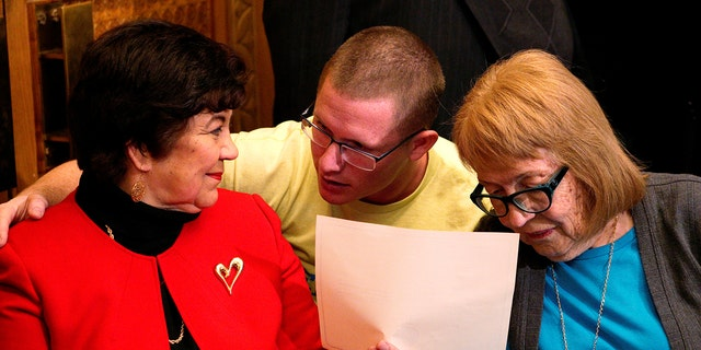Electoral College electors (L-R) Sen. Polly Baca, Michael Baca and Ann Knollman talk before taking the oath of office in the Governor's office at the State Capitol in Denver, U.S. December 19, 2016. REUTERS/Rick Wilking