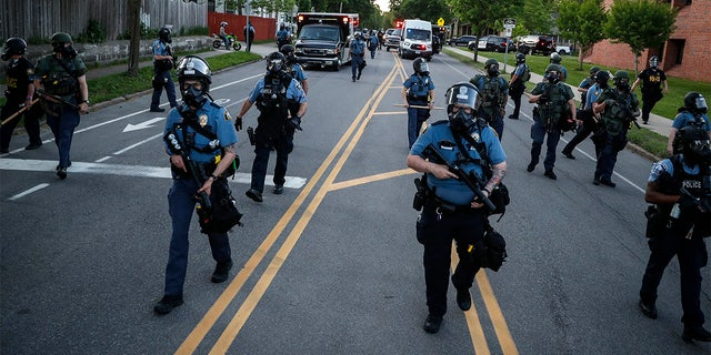 Police officers clear a section of Hamline Avenue in riot gear, Thursday, May 28, 2020, in St. Paul, Minn. (AP Photo/John Minchillo)