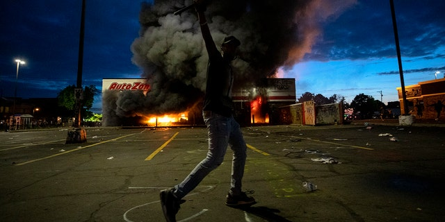 A man poses in the parking lot of an AutoZone store in flames, while protesters hold a rally against the death of George Floyd in Minneapolis on May 27. (Carlos Gonzalez/Star Tribune via AP)