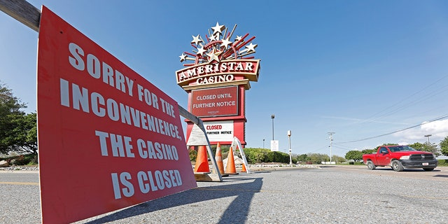 Traffic passes the closed Ameristar Casino in Vicksburg, Miss., Tuesday, March 17, 2020. All of Mississippi's state-regulated casinos were ordered closed by midnight Monday to limit the spread of the new coronavirus. (AP Photo/Rogelio V. Solis)