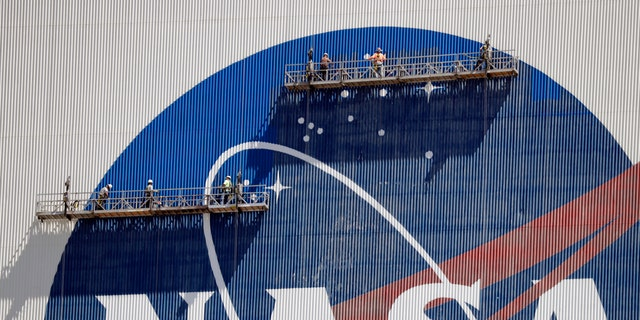 Workers near the top of the 526 ft. Vehicle Assembly Building at the Kennedy Space Center spruce up the NASA logo standing on scaffolds in Cape Canaveral, Fla., Wednesday, May 20, 2020.