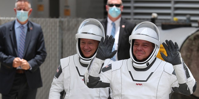 NASA astronauts Bob Behnken (R) and Doug Hurley (L) walk out of the Operations and Checkout Building on their way to the SpaceX Falcon 9 rocket with the Crew Dragon spacecraft on launch pad 39A at the Kennedy Space Center on May 27, 2020 in Cape Canaveral, Florida.