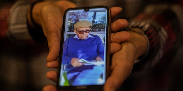 In this Monday, May 18, 2020 photo, Elena Valero shows a picture of her father Alonso Valero, 96, in Madrid, Spain. Alonso Valero was one of the residents at the Usera Center for the Elderly, who died during the coronavirus outbreak in Spain. (AP Photo/Bernat Armangue)