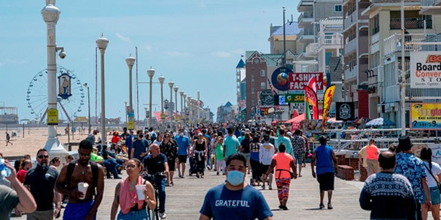 People enjoy the boardwalk during the Memorial Day holiday weekend amid the coronavirus pandemic on May 23, 2020 in Ocean City, Maryland. (Photo by ALEX EDELMAN/AFP via Getty Images)