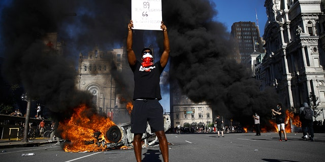 A vehicle is on fire behind a protester holding a sign during a rally on Saturday, May 30, 2020, in Philadelphia, over the death of George Floyd, a black man who died after being taken into police custody in Minneapolis. (AP Photo/Matt Rourke)
