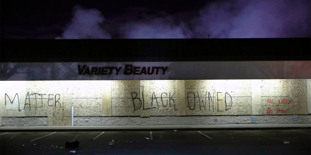 "A business labeled ""Black Owned"" remains untouched by looters, Friday, May 29, 2020, in Minneapolis. Protests continued following the death of George Floyd, who died after being restrained by Minneapolis police officers on Memorial Day. (AP Photo/John Minchillo)"