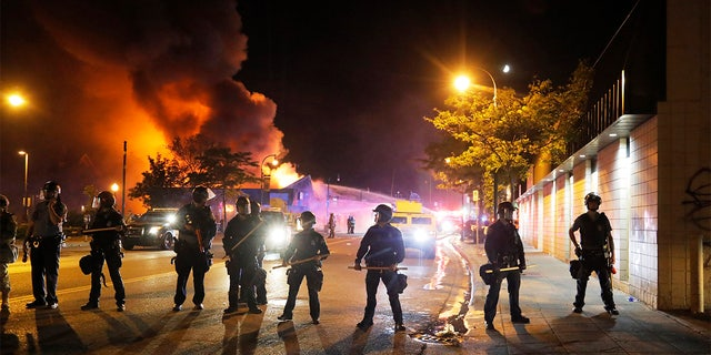 Police stand watch as a firefighters put out a blaze Saturday, May 30, 2020, in Minneapolis. AP Photo/Julio Cortez