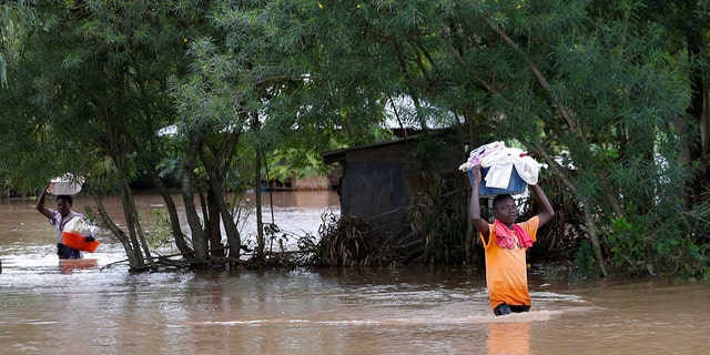 Residents carry their belongings inside flood water as they evacuate from their home after River Nzoia burst its banks and due to the backflow from Lake Victoria, in Nyadorera, Siaya County, Kenya May 2, 2020.