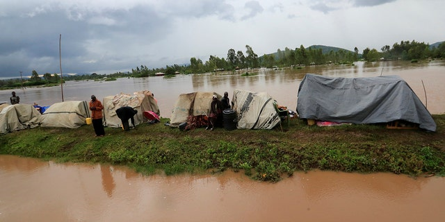 Residents set up makeshift shelter on a raised ground near floodwater, after they evacuated from their homes after River Nzoia burst its banks and due to the backflow from Lake Victoria, in Nyadorera, Siaya County, Kenya May 2, 2020.