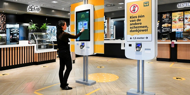 A woman uses a touch screen at a prototype location of fast-food giant McDonald's for restaurants which respect the 1.5m social distancing measure, amid the coronavirus disease (COVID-19) outbreak, in Arnhem, Netherlands, May 1, 2020.