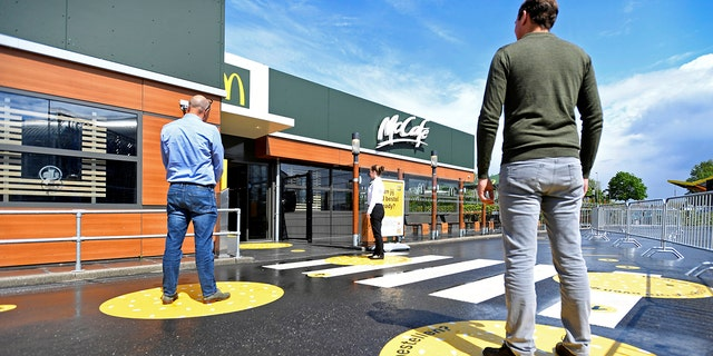 Customers wait outside on social distancing markings at a prototype location of fast-food giant McDonald's for restaurants which respect the 1.5m social distancing measure, amid the coronavirus disease (COVID-19) outbreak, in Arnhem, Netherlands, May 1, 2020.