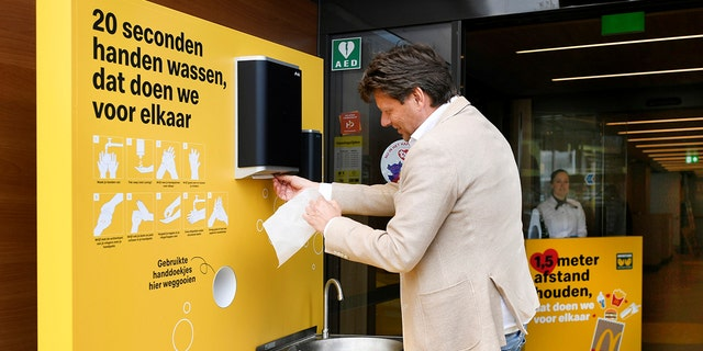 A customer cleans his hands before entering a prototype location of fast-food giant McDonald's for restaurants which respect the 1.5m social distancing measure, amid the coronavirus disease (COVID-19) outbreak, in Arnhem, Netherlands, May 1, 2020.