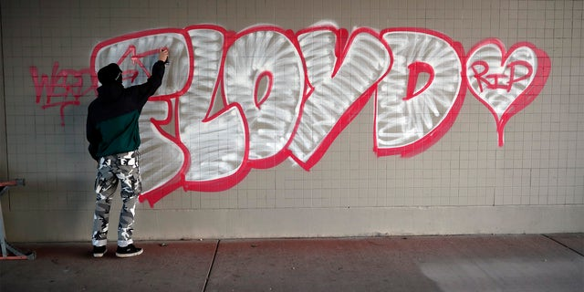 A protester spray paints George Floyd's name Friday, May 29, 2020, in Minneapolis. (Associated Press)