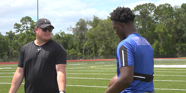 Kolby Tackett (left), Head Football Coach at Mount Dora Christian Academy, speaks with his quarterback, Tyquan Wiggins (Robert Sherman, Fox News)