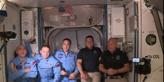 NASA astronauts Doug Hurley (right) and Bob Behnken (second right) after boarding the International Space Station, where they were welcomed by fellow astronaut and Expedition 63 Commander Chris Cassidy (center) and Russian cosmonauts Anatoly Ivanishin (left) and Ivan Vagner (second left).