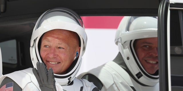 NASA astronauts Bob Behnken (R) and Doug Hurley sit in a Tesla vehicle after walking out of the Operations and Checkout Building on their way to the SpaceX Falcon 9 rocket with the Crew Dragon spacecraft on launch pad 39A at the Kennedy Space Center on May 30, 2020 in Cape Canaveral, Florida.
