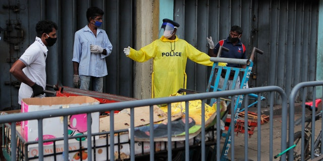 A Sri Lankan police officer in protective suit directs porters outside a market place in Colombo, Sri Lanka, on May 11.