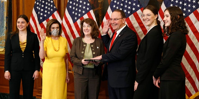 House Speaker Nancy Pelosi of Calif., second from left, wears a face mask to protect against the spread of the new coronavirus as she conducts a ceremonial swearing-in for Rep. Tom Tiffany, R-Wis., third from right, joined by his wife Chris, center, and daughters Lexie, from left, Karlyn and Katherine on Capitol Hill in Washington, Tuesday, May 19, 2020. (AP Photo/Patrick Semansky)