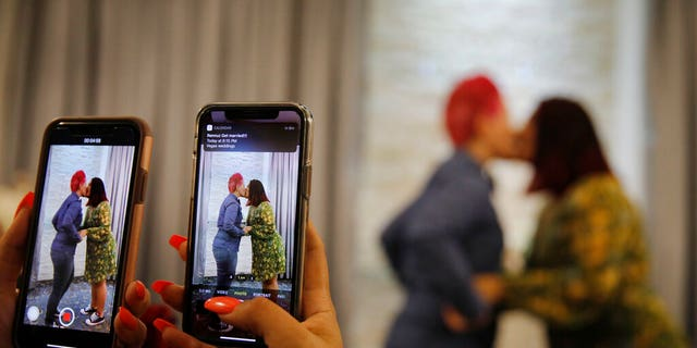 Cynthia Sanchez takes video and pictures as her sister Jennifer Escobar, right, and Luz Sigman celebrate their wedding ceremony at Vegas Weddings. (AP Photo/John Locher)