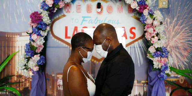 LaTahja Frazier, left, and Laborskie Frazier pose for their wedding photographer after getting married at The Little Neon Chapel, Sunday, May 10, 2020, in Las Vegas. (AP Photo/John Locher)