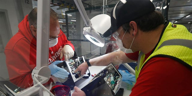 Ford Motor Co., team leader Kyle Lenart, right, inspects a ventilator that the automaker is assembling at the Ford Rawsonville plant, Wednesday, May 13, 2020 in Ypsilanti Township, Mich. The plant was converted into a ventilator factory, as hospitals battling the coronavirus report shortages of the life-saving devices. The company has promised to deliver 50,000 by July 4. Lenart is volunteering to make ventilators at the plant outside Detroit that, beginning Monday, will phase back into producing automotive components. (AP Photo/Carlos Osorio)