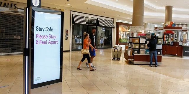 Signage encourages social distancing as Penn Square Mall reopens to the public Friday, May 1, 2020, in Oklahoma City. The mall has been closed since mid-March due to coronavirus concerns.