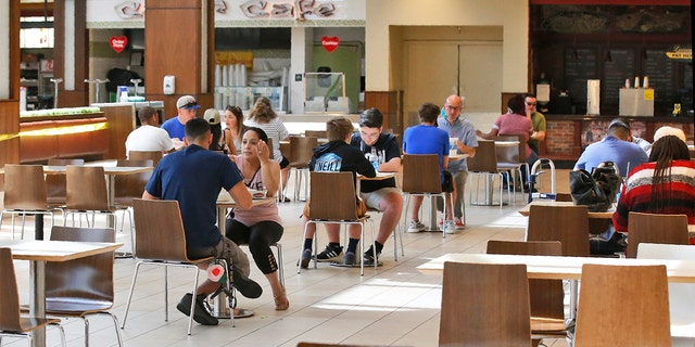 People eat in the food court at Penn Square Mall as the mall reopens Friday, May 1, 2020, in Oklahoma City. The tables in the food court have been thinned out, reducing capacity from from 600 to 170 seats.
