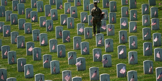 "FILE -- May 23, 2019:An Old Guard takes part in ""Flags-In"", an annual event where a small American flag is placed in front of more than 240,000 headstones of U.S. service members buried at Arlington National Cemetery in Arlington, Va. (REUTERS/Kevin Lamarque)"