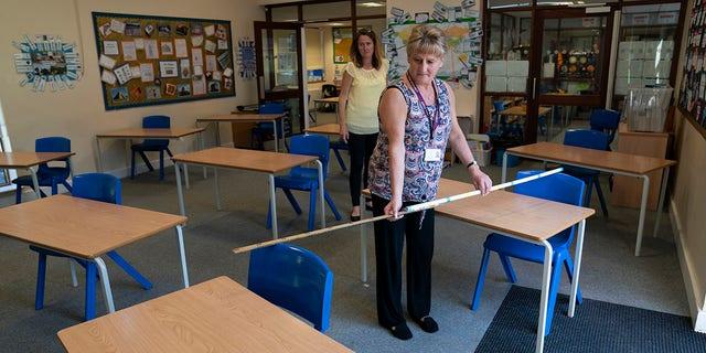Cô giáo lớp 6 Jane Cooper kiểm tra khoảng cách chỗ ngồi trong lớp học vì các biện pháp được thực hiện để ngăn chặn sự lây truyền coronavirus trước khi có thể mở lại trường tiểu học Lostock Hall ở Poynton gần Manchester, Anh, thứ Tư ngày 20 tháng 5 năm 2020. (Ảnh AP / Jon Super)