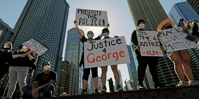 People hold signs during a protest over the death of George Floyd in Chicago, Saturday, May 30, 2020.
