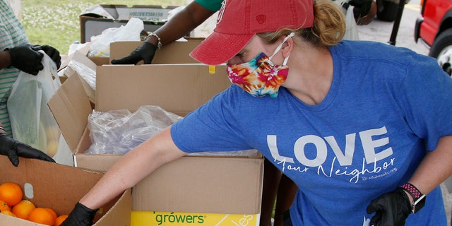 Candice Hillenbrand, of St. Luke's United Methodist Church and Ending Hunger OKC, reaches for an orange to add to a produce bag at a food give-away at Christ Temple Community Church, April 28, in Oklahoma City, as the need for food assistance grows during the coronavirus pandemic. (AP Photo/Sue Ogrocki)