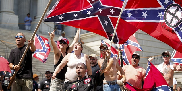 Members of the Ku Klux Klan yell as they fly Confederate flags during a rally at the statehouse in Columbia, South Carolina July 18, 2015.