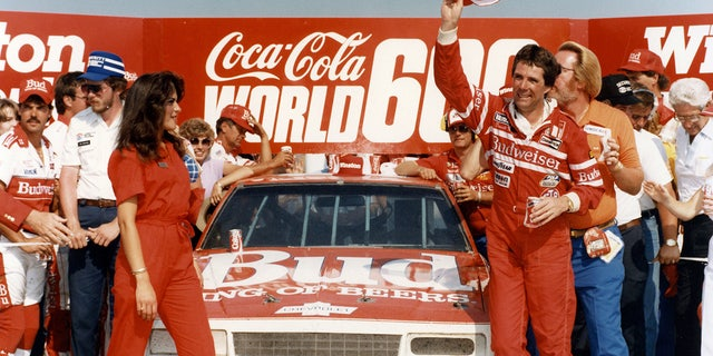 CHARLOTTE, NC — May 26, 1985: Darrell Waltrip waves his cap in victory lane at Charlotte Motor Speedway after winning the Coca-Cola World 600 NASCAR Cup race, one of three Cup victories Waltrip had during the year on his way to a third NASCAR Cup championship. (Photo by ISC Images & Archives via Getty Images)