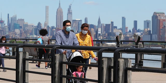 A general view of people wearing masks walking on the promenade as New Jersey continues with its Phase 1 of reopening the state during the Coronavirus (COVID-19) pandemic on May 16, 2020, at Liberty State Park in Jersey City, NJ.