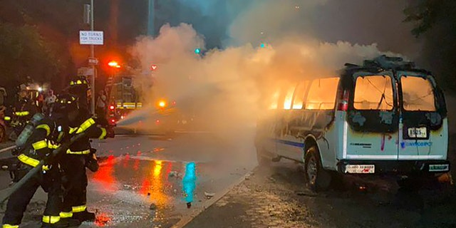 In this photo provided by Khadijah, firefighters work to contain the flames from a New York City Police Department van ablaze, Friday, May 29, 2020, in the Brooklyn borough of New York, amid a protest of the death of George Floyd in police custody on Memorial Day in Minneapolis. (Khadijah via AP)