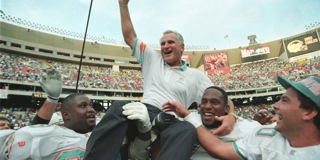 Miami Dolphins coach Don Shula is carried off the field by players Keith Sims (L) and Larry Webster (C) after Miami defeated Philadelphia 19-14 in Philadelphia November 14, 1993. This win made Shula the most successful coach in the league giving him his 325th career victory. (REUTERS/Gary Hershorn)