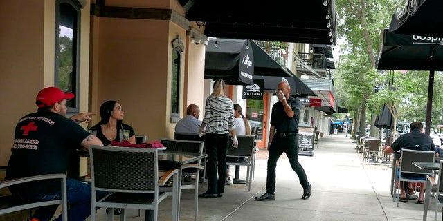 Customers enjoy sidewalk dinning in Orlando, Florida, Monday as restaurants could open at 50 percent capacity. (AP Photo/John Raoux)