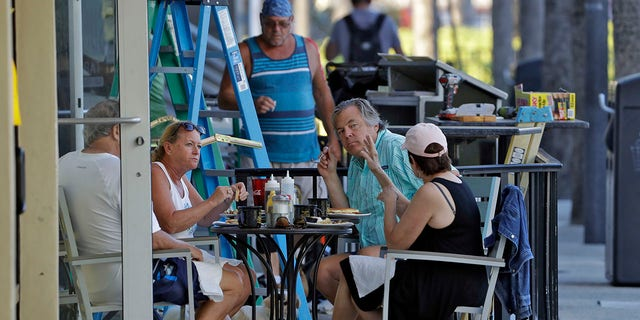 People have breakfast at a cafe Monday in Clearwater Beach, Fla., as many public beaches and restaurants begin reopening. (AP Photo/Chris O'Meara)