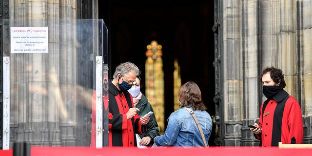 Believers arrive with online tickets for the first church service at Germany's famed Cologne Cathedral after coronavirus restrictions loosened in Cologne, Germany on Sunday. (AP Photo/Martin Meissner)