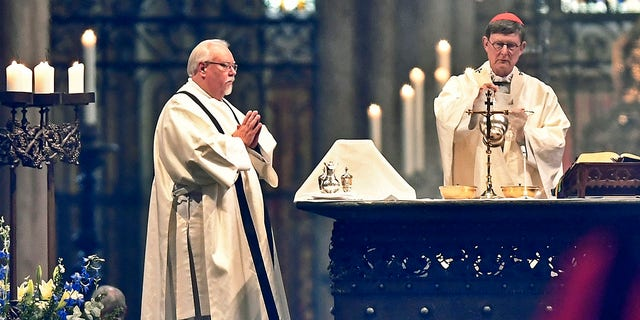 German Cardinal and Cologne Archbishop Rainer Woelki, right, celebrated the first church service at Germany's Cologne Cathedral on Sunday. (AP Photo/Martin Meissner)